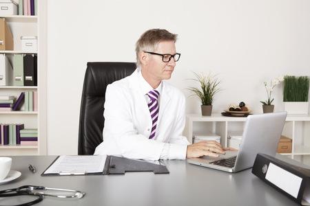 Mannelijke Arts die Laptop met behulp van medische rapporten