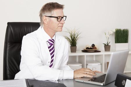 Ernstige Clinician Reading medische rapporten met laptop op tafel