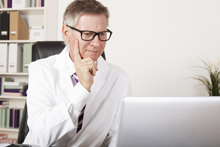 Medical Specialist Seriously Reading Diagnosis Reports at Computer photo