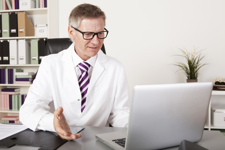 Middle Age Health Professional Talking Clients Progress using Laptop Stockfoto