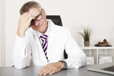 Sitting Male Doctor Not Feeling Well at his Table