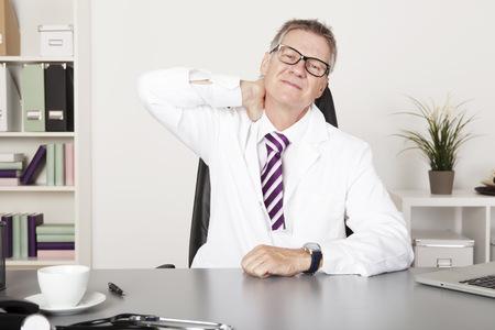 emphasizing: Tired Male Medical Doctor Holding his Back Neck Emphasizing Back Pain