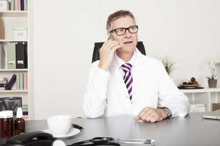 Male Physician Discussing to Clients Progress Through Phone photo