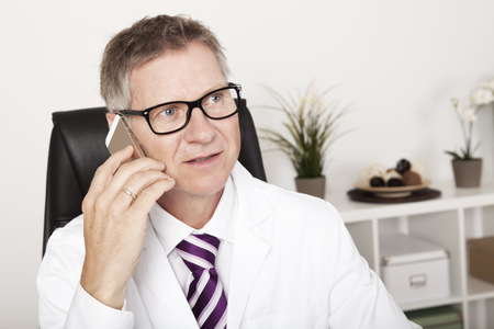 Male Doctor Seriously Calling Someone Using Phone photo