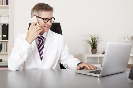 Medical Doctor Praten met Client Met behulp van telefoon tijdens het lezen bij Laptop