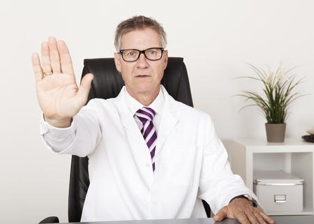 의자에 앉아있는 동안 손 정지 표시를 보여주는 심각한 닥터