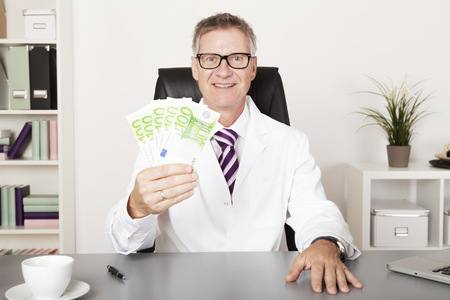 Happy Physician Holding Cash While Sitting Down photo