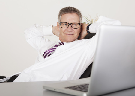 Male Clinician Seriously Viewing Something at Laptop on Table Stock Photo