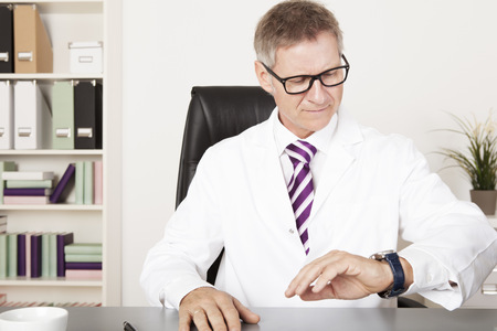 Male Physician Watching his Wrist Watch for Next Activity photo