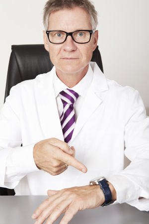 Serious Male Doctor Pointing his Wrist Watch, Looking at Camera photo