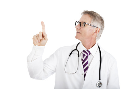 Middle-aged doctor in glasses and a white lab coat pointing above his head and looking up towards blank white copyspace