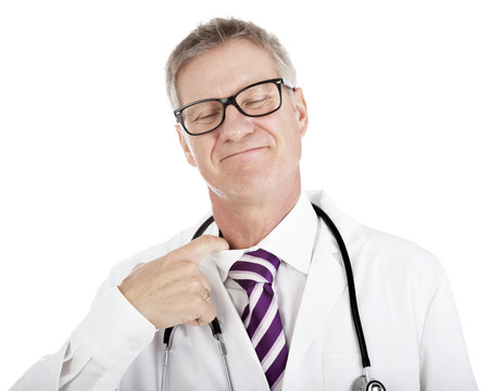 reacts: Smiling doctor loosening his tie by inserting his finger in the neck of his shirt as he reacts to the pressure and stress or to try to cool down on a hot day, isolated on white Stock Photo