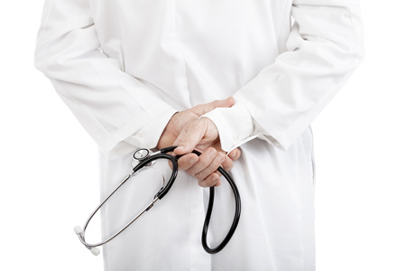 Doctor or nurse wearing a white lab coat holding a stethoscope behind his back , close up torso view on white