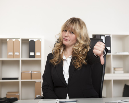 Attractive young businesswoman giving a thumbs down gesture as she shows her disapproval or indicates that she was unsuccessful in a venture photo