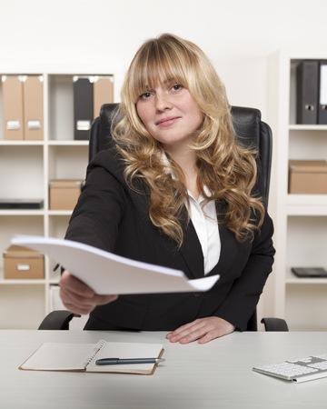 Mooie zakenvrouw overhandigen papierwerk haar hand uit te breiden tot de camera met een document met een vriendelijke glimlach