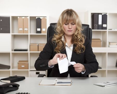 Young businesswoman sitting at her desk with a look of stern concentration tearing up a document showing her displeasure photo