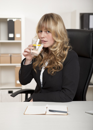Attractive businesswoman drinking a glass of refreshing water with a slice of tangy lemon as she sits at her desk in the office photo