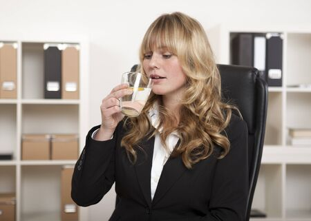Young office worker enjoying a glass of water and slice of lemon as she sits at her desk against a backdrop of files on shelves photo