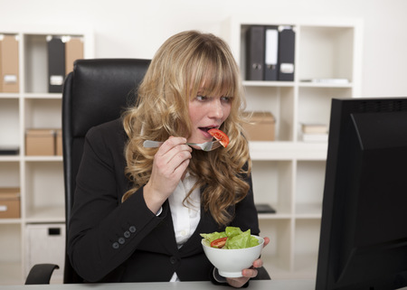 quick snack: Businesswoman having a quick snack at her desk eating a healthy green salad as she continues reading information on her computer monitor Stock Photo