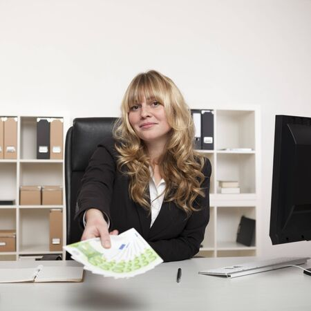 gives: Beautiful young businesswoman holding out a fistful of banknotes as she stretches across her desk conceptual of success, a bribe or pay-off Stock Photo
