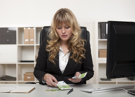 Businesswoman lub menadżerka licząc pieniądze na jej biurko sprawdzanie na płatności dla bankowości