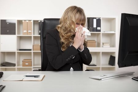 Businesswoman suffering from a cold or hay fever blowing her nose at her desk with a tissue as she continues reading the screen of her computer photo