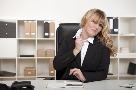 Beautiful young blond businesswoman under stress loosening her collar with a grimace as she sits at her desk photo