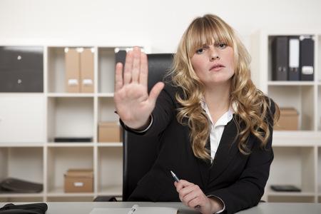 Jonge zakenvrouw bellen een halt houdt haar hand in de lucht met een strenge uitdrukking als ze zit achter haar bureau