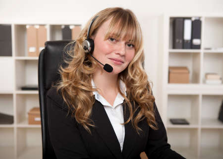 secretary phone: Friendly businesswoman wearing a headset looking at the camera with a lovely smile conceptual of a call centre, client services, reception or telemarketing