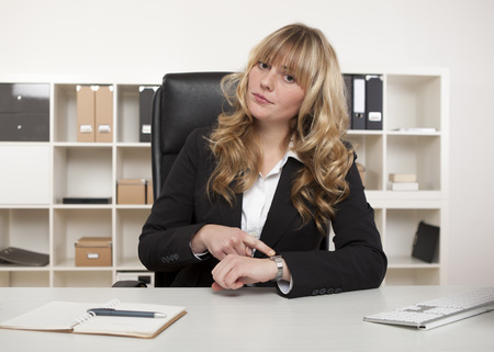 Manageress sitting at her desk in the office pointing to her watch making a point that someone is late for an interview of meeting with her Foto de archivo
