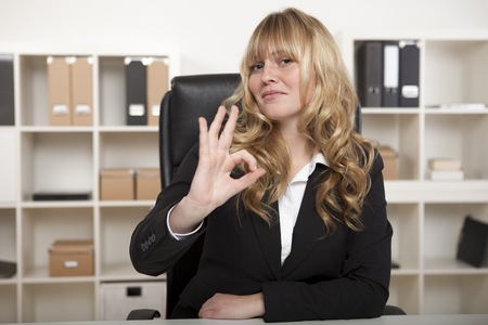 Happy attractive young businesswoman making a perfect gesture with her fingers as she gives the camera a pleased satisfied smile photo