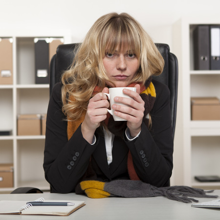 cold beverages: Young girl at work sitting at her desk in the office with a warm winter scarf around her neck enjoying a mug of hot coffee