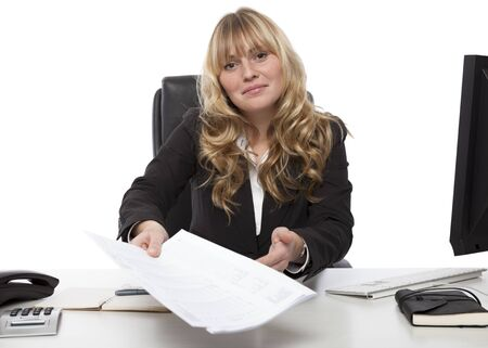 Smiling attractive young blond businesswoman handing over a document stretching over her desk with the papers in her hand photo