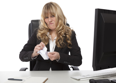 dissatisfaction: Disgusted businesswoman sitting at her desk ripping up a paper document with a grimace showing her dissatisfaction
