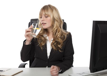 quench: Young businesswoman sitting at her desk drinking a glass of pure refreshing water and lemon to quench her thirst Stock Photo