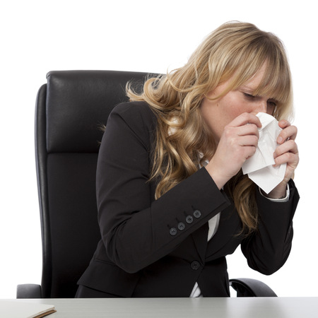 hanky: Young businesswoman with hayfever or seaonal cold and flu blowing her nose on a tissue as she sits at her desk, on white