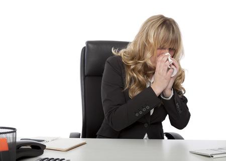 Zieke jonge onderneemster met een verkoudheid en griep zitten zat haar bureau op het werk waait haar neus op een tissue