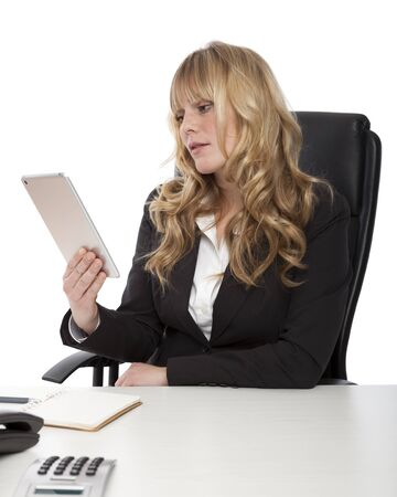 Attractive stylish young businesswoman using a tablet-pc as she sits at her desk reading information on the screen with a serious expression, on white photo