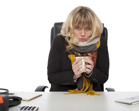 Freezing cold businesswoman wearing a knitted winter scarf sitting hunched up at her desk warming up with a mug of hot coffee, on white