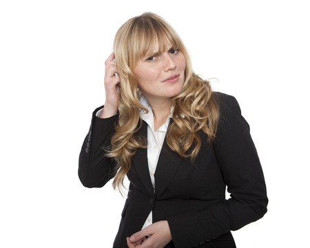 seeks: Puzzled young businesswoman scratching her head and looking at the camera with a perplexed quizzical expression as she seeks an explanation, on white