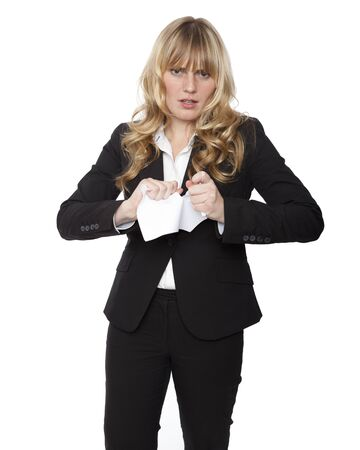 Young businesswoman tearing up a document with a look of disgust and frustration , three quarter pose isolated on white photo