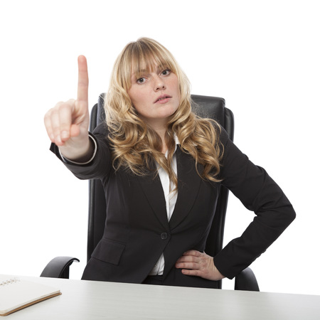 Manageress admonishing a junior employee waving her finger in the air with a stern expression, on white photo