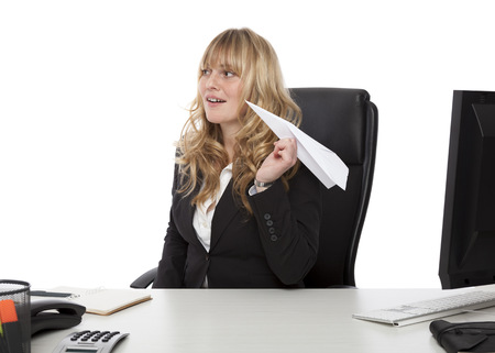 Mischievous businesswoman with a paper plane taking aim at a colleague as she sits at her desk with a look of playful anticipation, on white photo