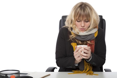 Cold businesswoman drinking hot coffee hunching over the hot liquid in a knitted winter scarf as she sits at her desk, on white
