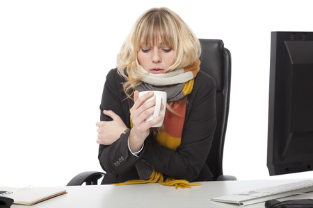 Koude zakenvrouw drinken van een kop hete koffie als ze zit te bibberen op haar bureau in een gebreide sjaal winter