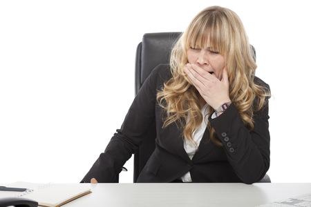 jornada de trabajo: Aburrido joven empresaria bostezando mientras espera que el final de su jornada de trabajo en la oficina, en blanco
