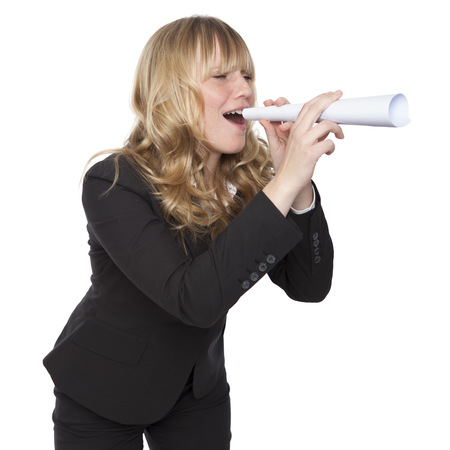 subordinates: Young businesswoman shouting through a paper tube simulating a megaphone as she playfully attracts the attention of a colleagues or subordinates in the office, on white