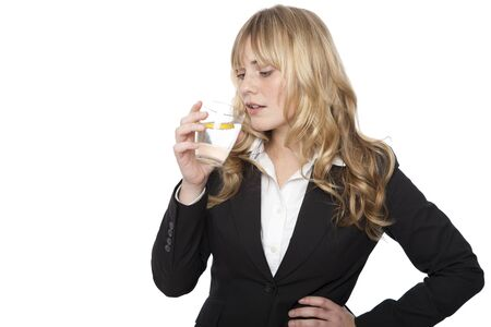 Young professional woman in a smart black jacket standing quenching her thirst drinking a glass of healthy pure water and lemon, on white photo