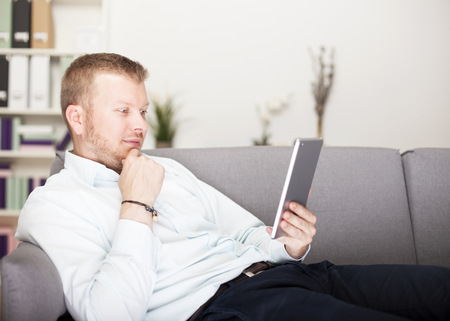 Thoughtful man reading his tablet computer as he relaxes on a couch with his hand to his chin and a pensive expression photo