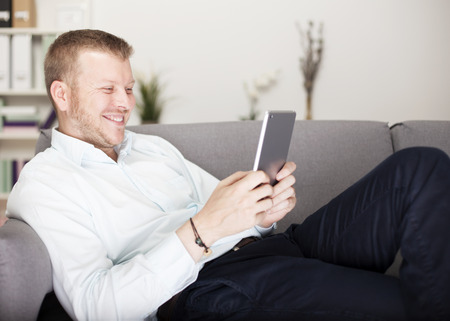 Man relaxing on a comfortable sofa smiling happily as he reads his tablet computer with a look of amused delight photo